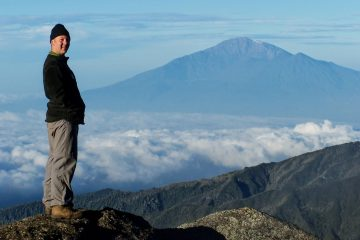 Henry Malmgren stands in front of Mt. Meru.