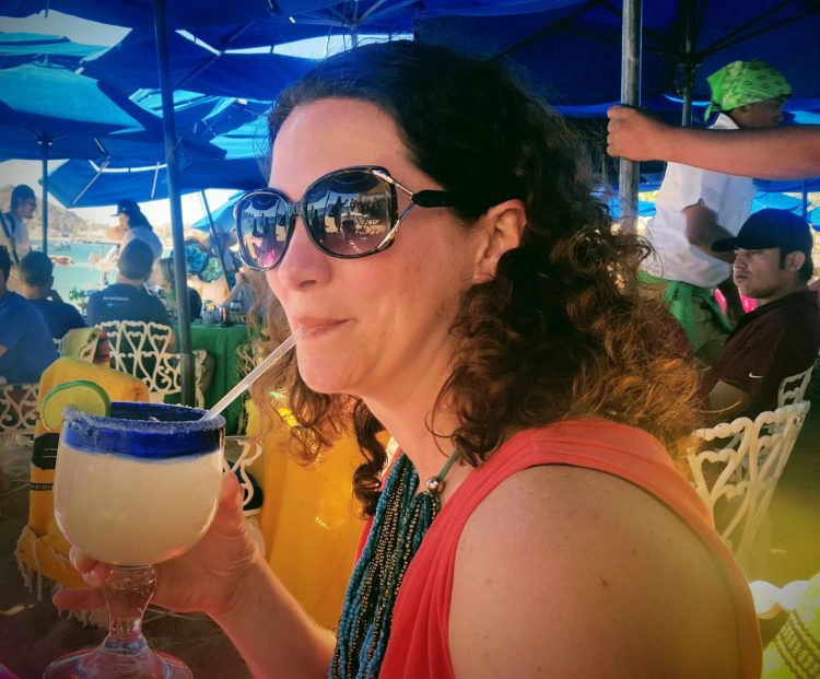 Darcie Eddy drinking a margarita at a beach restaurant.