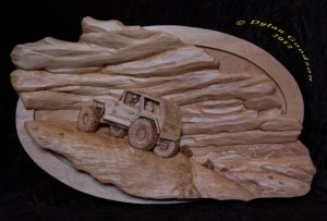 pictorial relief scene of a rock climbing jeep with mountains and clouds in the background
