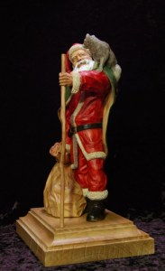 Santa Claus with a raccoon on his shoulder holding a walking stick carved by dylan goodson