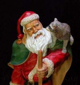 Santa Claus looking at the raccoon on his shoulder carved by dylan goodson