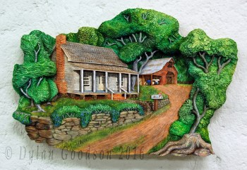 pictorial relief carving of the classic american farmhouse with a barn in the background painted with vibrant colors that suggest it's springtime