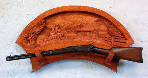 Gun rack with a relief scene carved into it featuring cowboys and a log cabin.