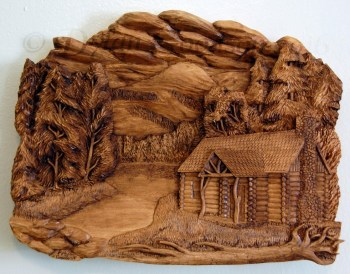 Relief carving of log cabin with mountains, trees and a lake in the background. Titled Northwoods Cabin