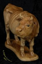 Cow standing looking to the right carved by dylan goodson