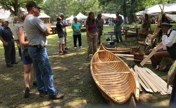 Ray Boessel Jr (far right) demonstrated and explained his methods used to construct a birch bark canoe in Native American style.