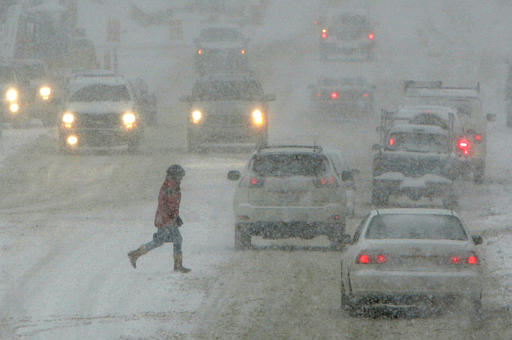Through a blinding snow storm, a woman crosses the street in downtown Chagrin Falls, Ohio, Saturday morning, Jan. 22, 2005.  Northeast Ohio was expecting up to a foot of snow in the major winter storm. (AP Photo/Amy Sancetta)