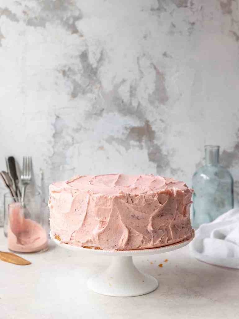 sumac roasted strawberry layer cake on a stand