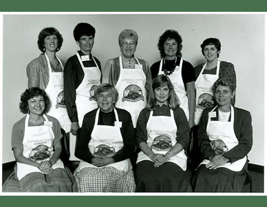 Nine women in aprons
