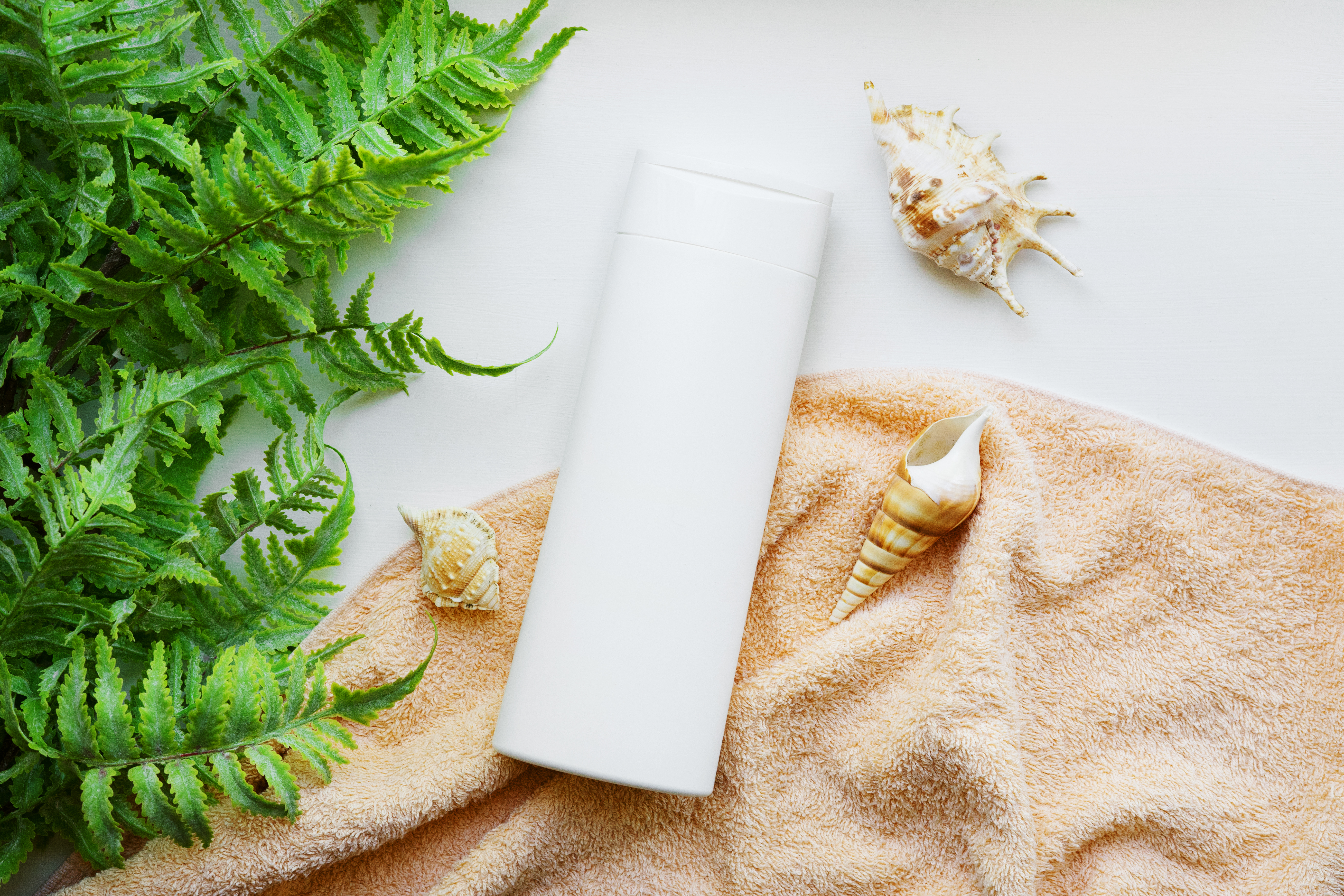 white-bottle-brand-free-shampoo-beige-towel-with-shells-seaweed-hair-care-products-with-marine-elements