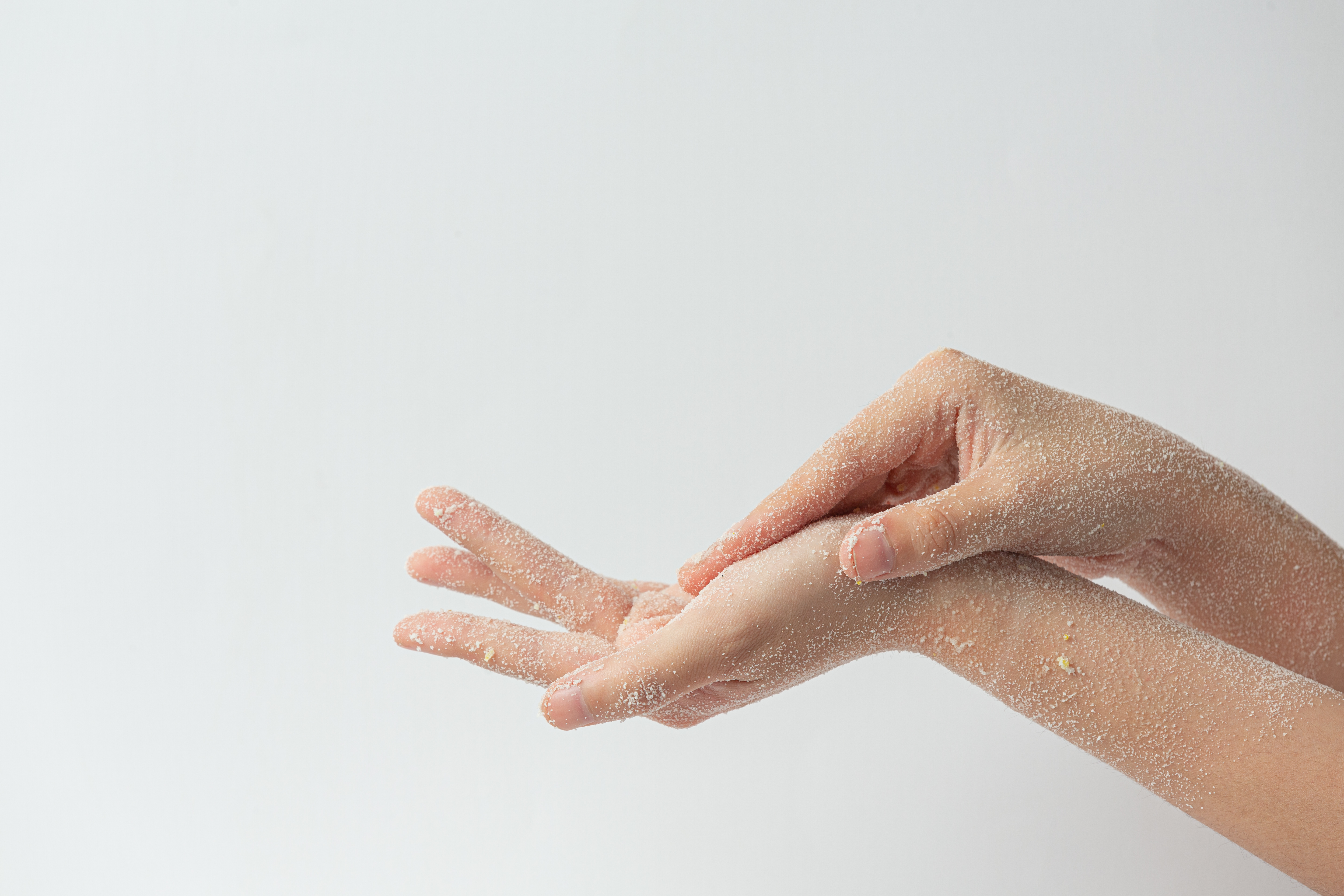 Young woman applying natural lemon scrub on hands against white