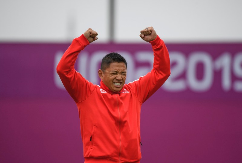An athlete raises his arms in victory
