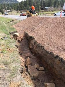 Pile of dirt next to trench in median of highway