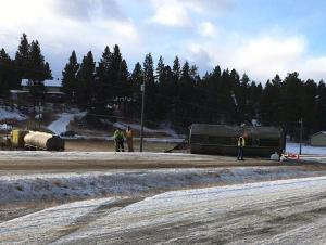 Tanker truck in snow-covered grass off the highway and a tanker trailer on its side on a snow-covered highway with workers milling around
