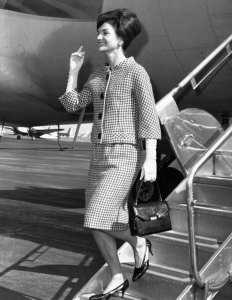 Jackie Kennedy en tailleur élégant pied-de-poule, descendant de l'avion à l'aéroport de New-York. Elle est coiffée d'un chignon chic et arbore un grand sourire.