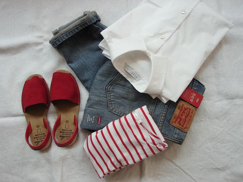 Chaussures rouges, chemise et jean sur un drap blanc