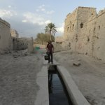 Standing on the falaj in the old village in Manah
