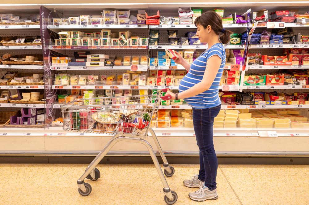 femme enceinte choisissant son fromage dans un rayon de supermarché