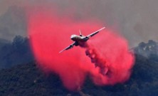 This Saturday, July 8, 2017, photo released by the Santa Barbara County Fire Department shows a DC-10 making a fire retardant drop on a ridge line along the eastern flank of the Alamo Fire in Santa Barbara County, Calif. Wildfires barreled across the baking landscape of the western U.S. and Canada, destroying a smattering of homes, forcing thousands to flee and temporarily trapping children and counselors at a California campground. Southern California crews hope slightly cooler temperatures and diminishing winds will help in the battle Sunday. (Mike Eliason/Santa Barbara County Fire Department via AP)