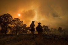 CalFire firefighter Jake Hainey, left, and engineer Anna Mathiasen watch as a wildfire burns near Oroville, Calif., on Saturday, July 8, 2017. The fast-moving wildfire in the Sierra Nevada foothills destroyed structures, including homes, and led to several minor injuries, fire officials said Saturday as blazes threatened homes around California during a heat wave. (AP Photo/Noah Berger)
