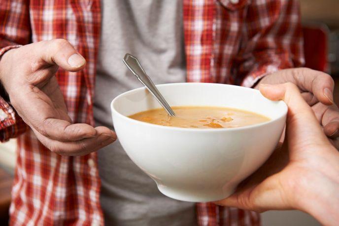 una persona dandole a otra un tazón con sopa