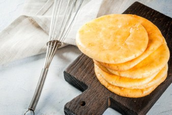 Dietary healthy food. The concept of low-gluten gluten-free non-allergic snack. Homemade freshly baked tortillas cloud bread, from eggs and cream cheese. On light concrete table copy space