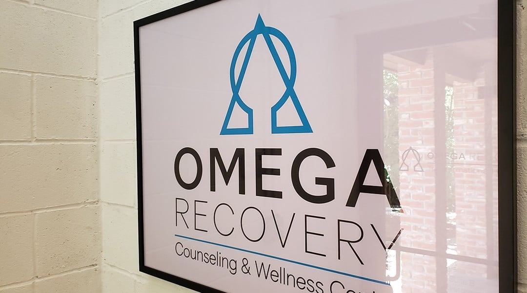 Photo of an Omega Recovery sign from inside main office by South Lamar