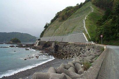 Tipik bir sahil kıyısı, arkada toprak kaymasına karşı beton ızgaralarla korunmuş yamaç