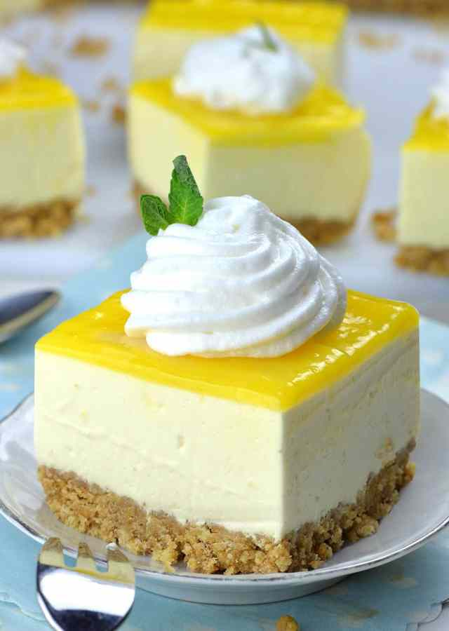 Piece Of No Bake Lemon Cheesecake Bar On A White Plate With Cool Whip Topping In