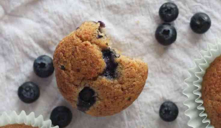 keto blueberry muffins for easter with blueberries scattered on a tablecloth.