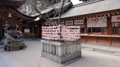Temizuya till vänster, omikuji-spådomar i mitten och en ställ för omamori-amuetter till höger
