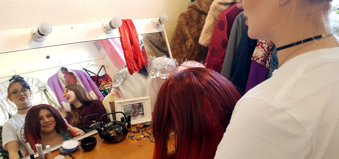 [Image shows hair and make-up stylist Emmie adjusting the red wig that Robert is wearing. We see both their reflections in the mirror, smiling and talking. We also see assistant Director Ellie, laughing and looking towards them. The mirror is framed by lights, and we see a framed photo of The Fabulous Josh on the table in front of them. In the reflection, we see several sparkly outfits including a pride flag leotard]