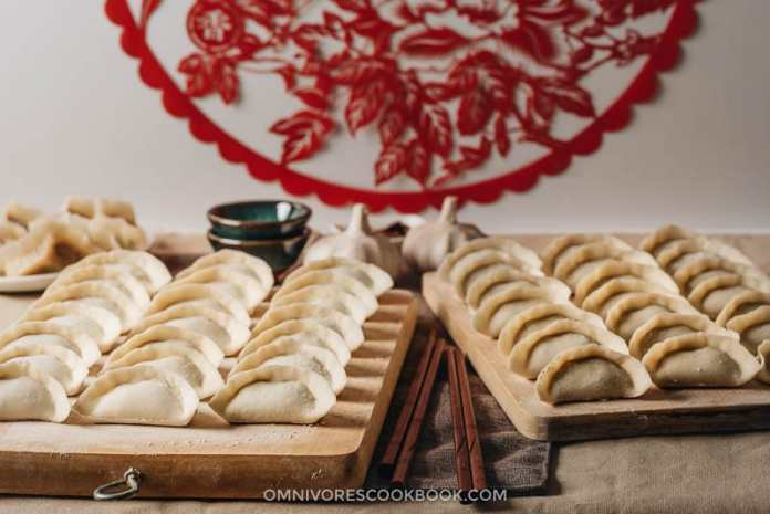Uncooked Chinese dumplings on cutting boards