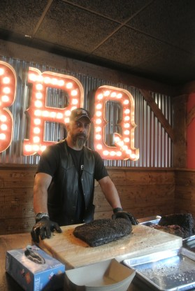 Pitmaster Nestor ready to cut into a perfect brisket at Hoodoo Brown BBQ in Ridgefield