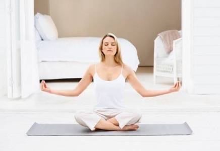 Pretty young girl mediating by her bedroom