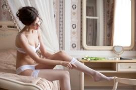 Beautiful bride putting on stockings