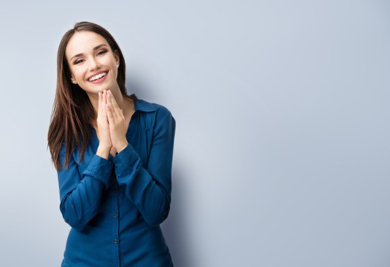 Portrait of happy gesturing smiling young woman in casual smart blue clothing, on grey, with copyspace area for text or slogan