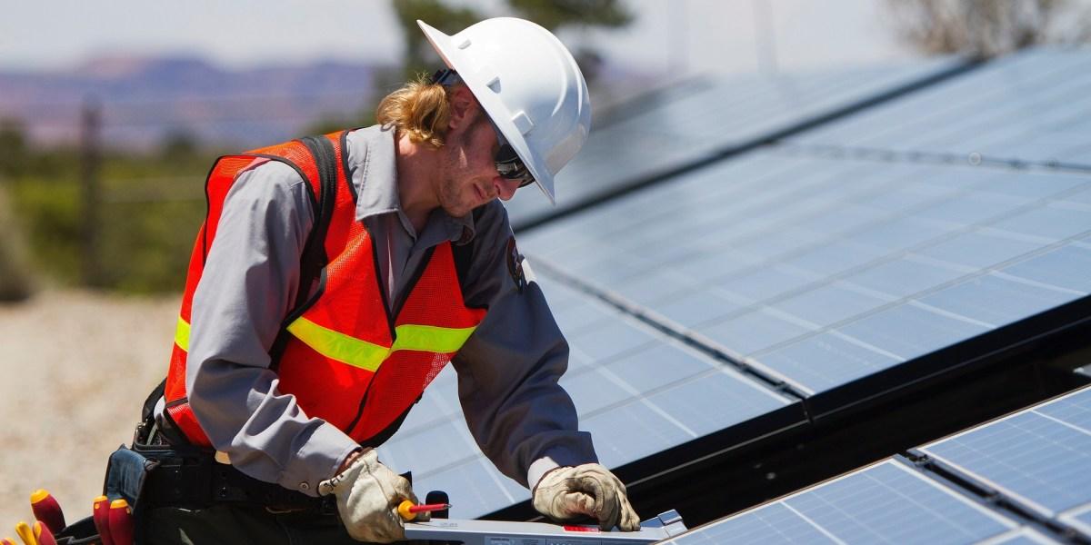 Crédito para programa de eficiência energética em Curitiba: homem instalando painel solar