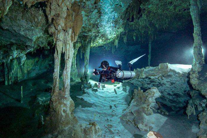 Sidemount Taucher in der Höhle