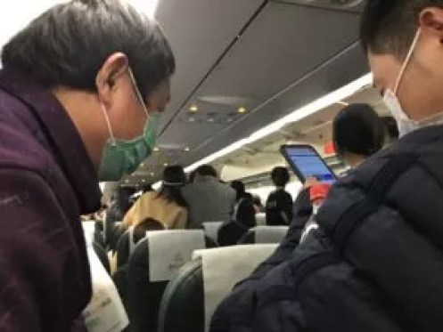 Chinese air passengers in masks take video of something going on in the back of the plane.