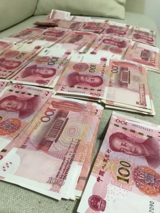 piles of Chinese RMB - how to save money for travel a working class guide - onaroadtonowhere.com