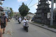 Photo de balinais en habits traditionnels, sortant d'un temple en scooters. Notez les offrandes écrasées aux pieds de Julien