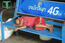 Un garçon en train de dormir sur un banc dans la gare