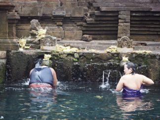 Des fidèles se purifient sous l'une des 13 trompes alimentant les piscines