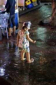 Une petite fille joue dans la pluie