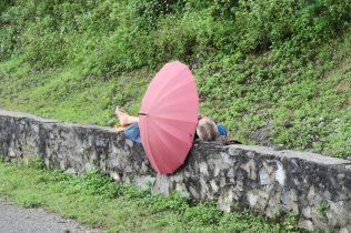 Un homme se reposant sur le muret qui bordait la route