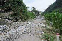 Souvent la route est en mauvais état : ici, il n'y a carrément plus de goudron. Il faut alors naviguer sur des grosses pierres saillantes...