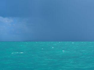 """La mer turquoise et au loin une """"shower"""""""