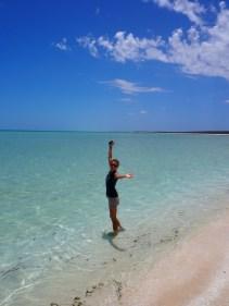 Elise trempe ses pieds dans l'eau translucide de shell beach