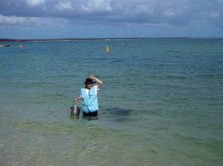 Une volontaire fait le signe (point sur la tête) indiquant qu'il ne lui reste qu'un poisson. Les autres volontaires se coordonnent alors pour tous donner le dernier poisson en même temps.